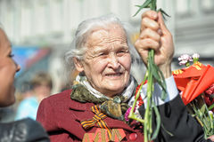 Old woman veteran of WWII. An unidentified elderly woman veteran of WWII watches at the parade on annual Victory Day, May, 9, 2013 royalty free stock photo