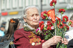 Old woman veteran of WWII. An unidentified elderly woman veteran of WWII watches at the parade on annual Victory Day, May, 9, 2013 royalty free stock photos