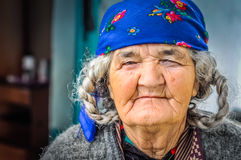 Old woman with violet headcloth in Tajikistan. Khorog, Tajikistan - circa October 2011: Older woman with grey braids of hair fasten by violet headcloth in Khorog Royalty Free Stock Image