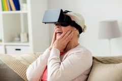 Old woman in virtual reality headset or 3d glasses. Technology, augmented reality, entertainment and people concept - senior woman with virtual headset or 3d Royalty Free Stock Images