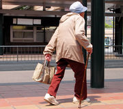 Old woman walking. An old woman with bag walking in a bus station-Japan Stock Image