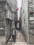 An old woman walking in the alley Stock Photos