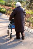 Old woman walking alone. Old woman uses her wagon and walks alone Royalty Free Stock Photo