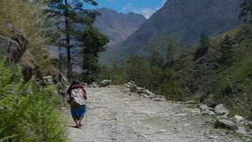 An old woman is walking along the road. An old woman walks the mountain road. Nepal stock footage