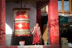 The old woman walking around the round buddhist drum royalty free stock photo