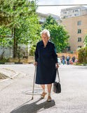 Old woman walking with a cane. Down the street of the city Stock Photo