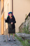 Old woman walking in the little town. With old stick alone Stock Photos