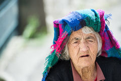 Old woman walking in the little town. With old stick alone Stock Images