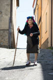 Old woman walking in the little town. With old stick alone Royalty Free Stock Photos