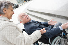 Old woman walking outdoors with husband in wheelchair Royalty Free Stock Photo