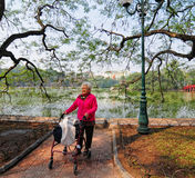Old woman walking at the park near Hoan Kiem lake in Hanoi, Vietnam Stock Photos
