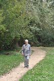 Old woman walking in a park. Outdoors Royalty Free Stock Photos