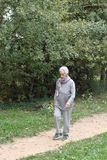Old woman walking in a park. Outdoors Royalty Free Stock Photography