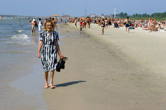 Old woman walking and relaxing in Crowded beach. LIEPAJA, LATVIA - JULY 9: Old woman walking and relaxing in Crowded beach. Liepaja, Latvia, summer 2006 Royalty Free Stock Images