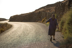 Old Woman walking on the road at the shore-line of Folegandros Royalty Free Stock Photo