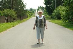 Old woman walking on the road at the sunny day. Old mature woman walking on the road at the sunny day. Positive emotions in lifestyle Royalty Free Stock Photos