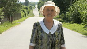 Old woman walking on the road at the sunny day stock footage