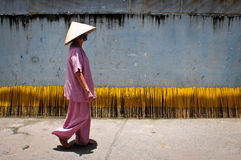 An old woman walking on rural road in Mekong Delta, Vietnam.  Royalty Free Stock Images