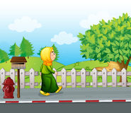 An old woman walking at the streetside with a mailbox Stock Images