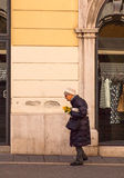 Old woman walking. TRIESTE, ITALY - MAY, 08: Old woman walking holding mimosa flowers during the International Women's Day on May 08, 2015 Royalty Free Stock Photo