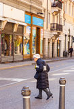 Old woman walking. TRIESTE, ITALY - MAY, 08: Old woman walking holding mimosa flowers during the International Women's Day on May 08, 2015 Royalty Free Stock Image