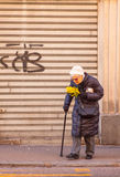 Old woman walking. TRIESTE, ITALY - MAY, 08: Old woman walking holding mimosa flowers during the International Women's Day on May 08, 2015 Royalty Free Stock Images
