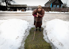 Old woman walking through the village. Belarus. Mature woman standing in the middle of the village, one of the last of a dying village residents vanishing Mars Royalty Free Stock Photos