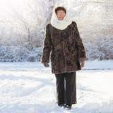 Old woman walking at winter park. Stock Photos