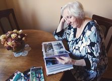 Old woman is watching an album with old photos. stock images