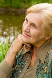 Old woman at water Royalty Free Stock Image
