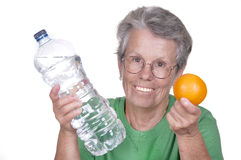 Old woman with water bottle and orange Royalty Free Stock Photo