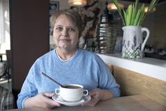 Old woman wearing blue sweater sitting in the cafe Royalty Free Stock Photos