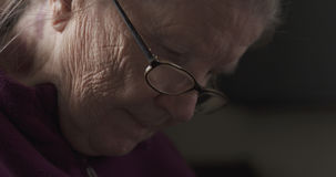 Old woman wearing glasses doing something. 4k photo Royalty Free Stock Photo
