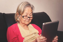 Old woman wearing glasses at home reading something tablet. Old woman wearing glasses seated on a sofa at home reading something on a touchscreen tablet Stock Image