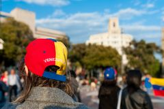 Old woman wearing hat with venezuelan flag and country name in Barcelona city main square during march for regime change. Woman wearing hat with venezuelan flag royalty free stock image