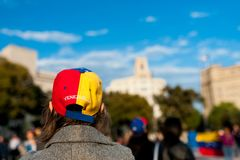 Old woman wearing hat with venezuelan flag and country name in Barcelona city main square during march for regime change. Wearing hat with venezuelan flag and stock photo