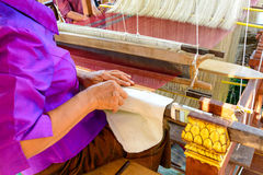 Old woman weaving silk on loom Stock Photo