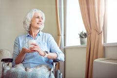 Old woman in wheelchair holding cup Stock Images