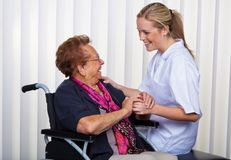 Old woman in a wheelchair and a nurse Stock Images