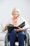 Old woman in wheelchair with photo album Royalty Free Stock Images