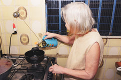 Old woman with white hair cooking at the kitchen Royalty Free Stock Image