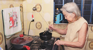 Old woman with white hair at kitchen using a hashi Royalty Free Stock Photography