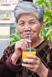 Old woman who drinking Orange juice Royalty Free Stock Photos