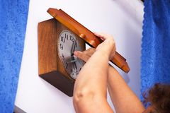 The old woman winds the old wall clock with the key. The symbol of the passage of time and the alternation of generations Royalty Free Stock Images