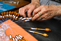 Old woman working on bobbin lace. On Brugge stock photography