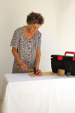 An old woman is working with a hammer Royalty Free Stock Photography