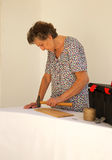 An old woman is working with a hammer Royalty Free Stock Photo