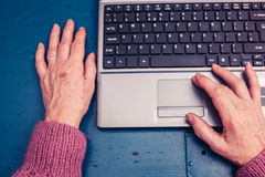 Old woman working on laptop computer at home Royalty Free Stock Photos