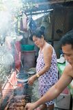 Old woman 80 year old asian cooking bbarbeque outdoors. 80-year old asian woman cooking BBQ barbeque outdoors in typical asian home. day time. Home-made barbeque Stock Images
