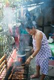 Old woman 80 year old asian cooking bbarbeque outdoors. 80-year old asian woman cooking BBQ barbeque outdoors in typical asian home. day time. Home-made barbeque Royalty Free Stock Photography